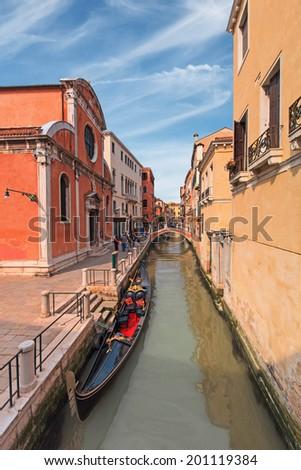 Traditional gondola parked in narrow venetian canal - stock photo
