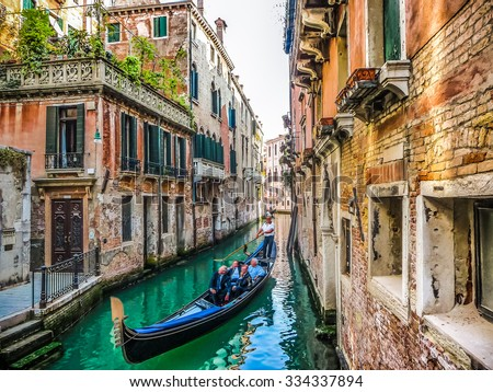 Traditional Gondolas on narrow canal between colorful historic houses in Venice, Italy - stock photo