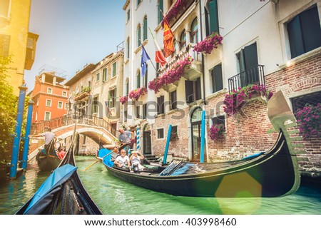 Traditional gondolas on narrow canal in Venice, Italy with retro vintage toned Instagram style grunge filter and lens flare sun light effect on a sunny day with blue sky in summer - stock photo