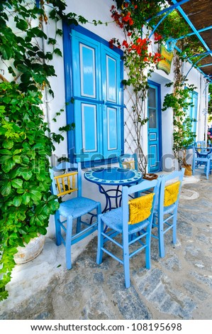 Traditional greek blue blinds and chairs on a small back street - stock photo