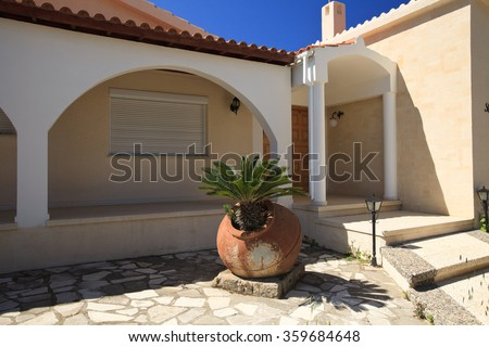 Traditional Greek courtyard decorated with clay pitcher and palm tree - stock photo
