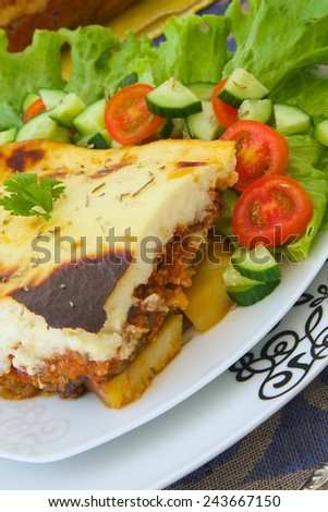 Traditional Greek dish - moussaka - aubergines and potatoes based dish. Served with fresh salad leaves,cherry tomatoes and cucumbers. Glass mold with entire dish is in the background. - stock photo