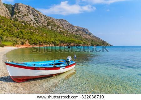 Traditional Greek fishing boat in sea bay on secluded beach, Samos island, Greece - stock photo