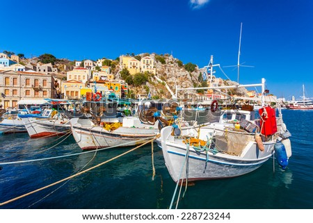 Traditional Greek fishing boats in harbour at Symi Town in the Dodecanese Greece Europe - stock photo