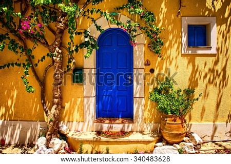 Traditional greek house with blue doors and yellow wall - stock photo