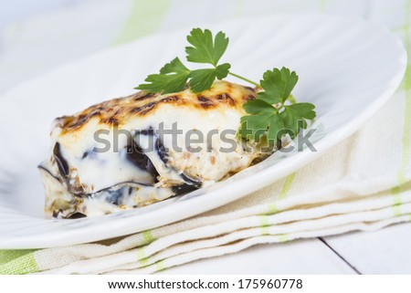Traditional Greek moussaka served and decorated with a leaf of parsley