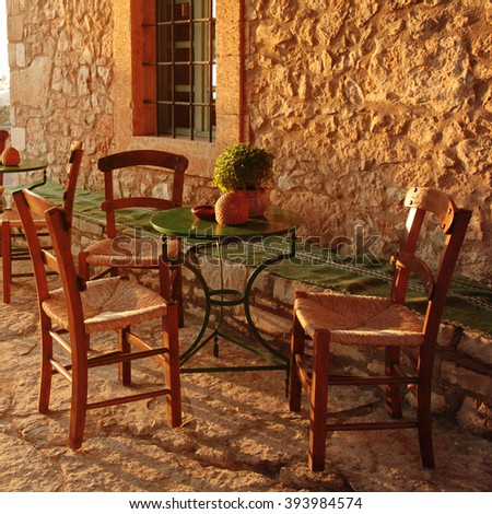 traditional greek outdoor restaurant on terrace, empty table at an street village restaurant, Crete, Greece. Sunset light, square image - stock photo