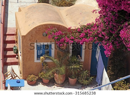traditional greek red building with patio and flowers of Oia village, Santorini island, Greece - stock photo