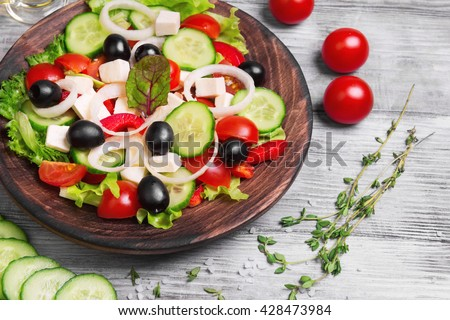 Traditional greek salad with fresh vegetables, feta cheese, black olives, and ingredients for cooking Greek salad oil, thyme, cherry tomatoes, cucumbers, salt - stock photo