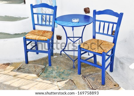 Traditional Greek Terrace With Blue Tables And Chairs In Pyrgos, Santorini,  Cyclades, Greece