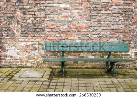 Traditional Green Bench Seat with Old Brick Wall in Background - stock photo