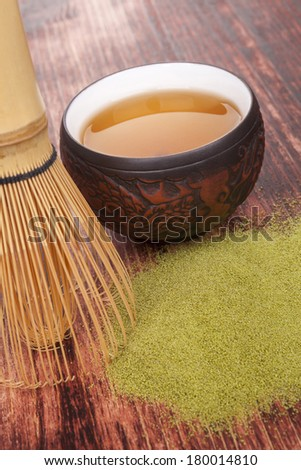 Traditional green powdered tea matcha on wooden background with bamboo chasen and cup of tea. Tea drinking.  - stock photo