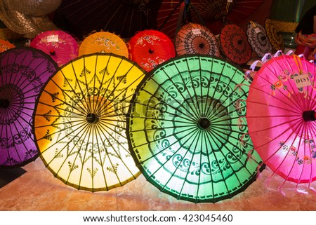 Traditional handicraft umbrellas are sold in night market in Bagan, Myanmar. - stock photo