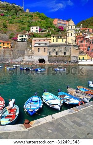Traditional harbor with small boats and Santa Margherita d'Antiochia church in Vernazza, Cinque Terre, Italy