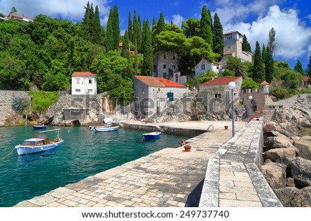 Traditional harbor with small boats surrounded by stone pier on the shores of Adriatic sea, Trsteno, Croatia - stock photo