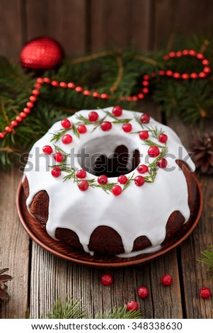 Traditional homemade christmas cake sweet holiday dessert with cranberry in new year tree decorations frame on vintage wooden table background. Rustic style