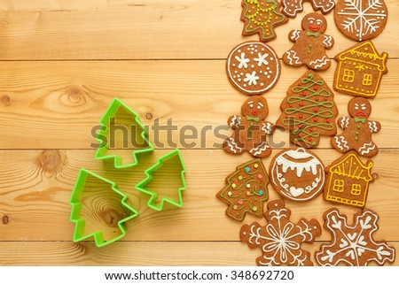 Traditional homemade Christmas gingerbread cookies and green plastic cutters on wooden table
