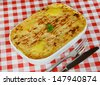 Traditional Homemade Fish Pie in a casserole dish with crispy mashed potato on the top on a red gingham tablecloth - stock photo