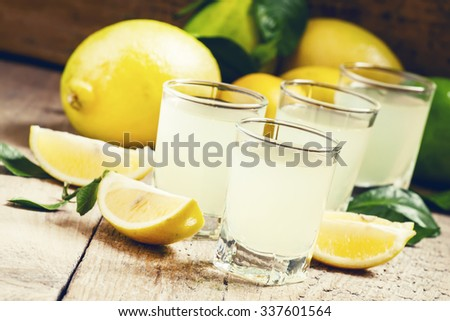 Traditional homemade lemon liqueur limoncello and fresh citrus on the old wooden background, selective focus