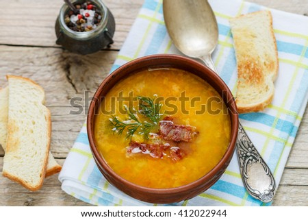 Traditional homemade  pea soup with bacon, herbs and croutons. Rustic style.  Selective focus.  - stock photo