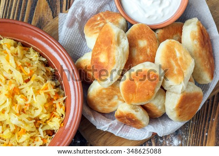 Traditional homemade pies with cabbage and sauerkraut on the plate on wooden board. Savory stuffed patties also known as pastel, pate or piroshki. Fried russian pastry pirozhki on wooden background. - stock photo