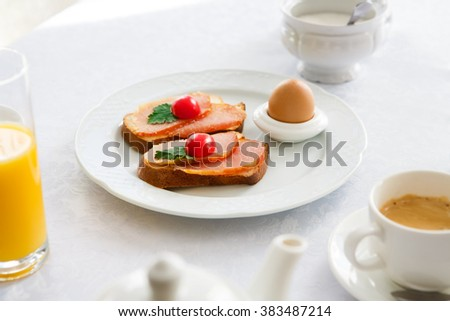 Traditional Hotel Breakfast served at white table with ham and cherry tomato toasts, boiled egg, orange juice and coffee - stock photo