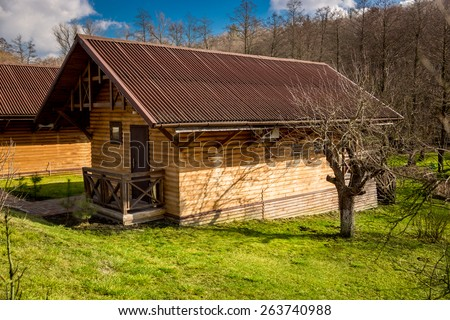 Traditional house made of wooden logs in forest at sunny day - stock photo