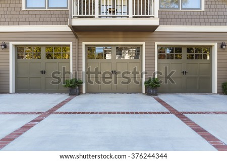 Traditional house with three single car garage  - stock photo