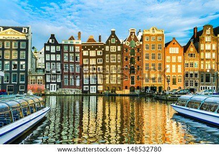 Traditional houses of Amsterdam with boats and reflections in the water - stock photo