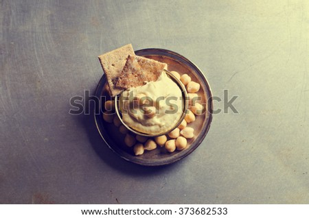 Traditional hummus with chickpeas and dry pieces of pita. Selective focus.