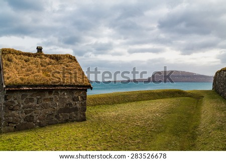 Traditional hut in the Faroe Islands with a green grass roof with a backdrop of the Atlantic ocean and an island - stock photo