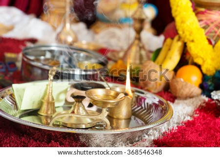 Traditional Indian Hindu religious praying items in ear piercing ceremony for children. Focus on the oil lamp. India special rituals heritage. - stock photo