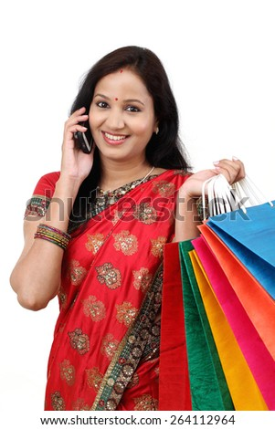 Traditional Indian woman holding shopping bags and talking on cellphone - stock photo