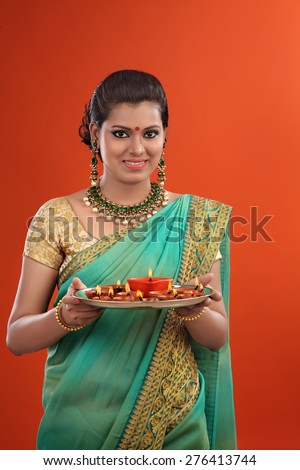 Traditional Indian woman holding the oil lamps - stock photo