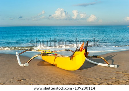 Traditional indonesian fishing boat on Bali ocean beach at sunset - stock photo