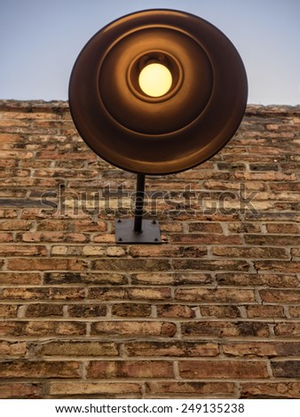 Traditional industrial copper light on brick wall. - stock photo