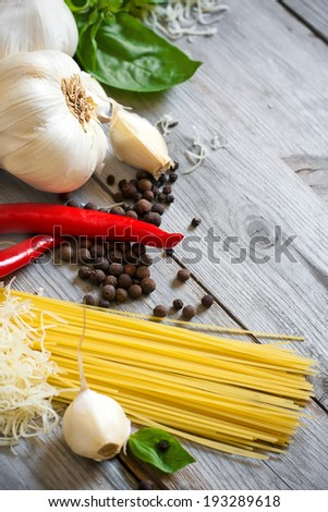 Traditional ingredients of italic cuisine - garlic, peppers, basil and grained parmigiano. Selective focus. - stock photo
