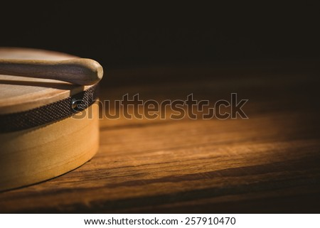 Traditional Irish bodhran and stick on wooden table - stock photo