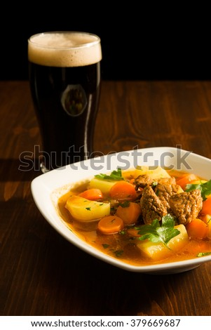 Traditional Irish Stew on a square plate with a pint of beer over a table.