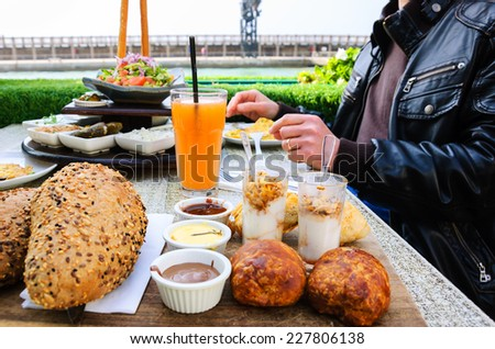 Traditional Israeli breakfast (eggs, vegetable salad, orange juice, pastries, yogurt with granola) at seaside cafe in Tel Aviv (Israel) Male hands with wedding ring. Selective focus on strawberry jam. - stock photo