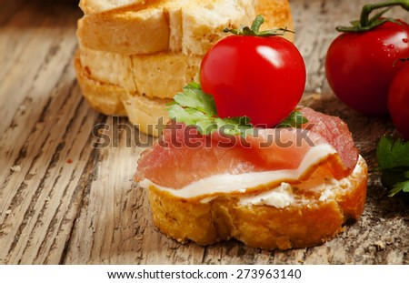 Traditional Italian antipasti crostini with ham, cheese and tomato, selective focus - stock photo