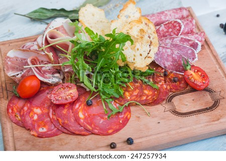 Traditional italian antipasto with prosciutto and different sorts sausage on a wooden table