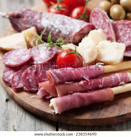 Traditional italian antipasto with prosciutto, cheese, olive and sausage, selective focus - stock photo