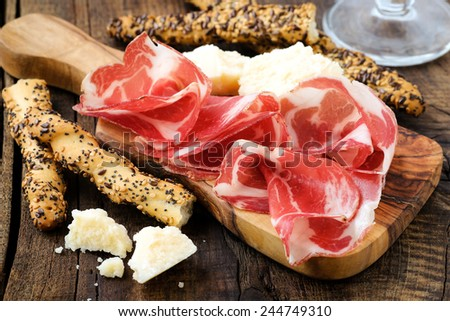 Traditional Italian appetizer - cured prosciutto ham or coppa on a wooden serving board with breadsticks and parmesan cheese - stock photo