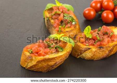 traditional italian bruschetta with chopped tomatoes in olive oil and basil garnishing - stock photo