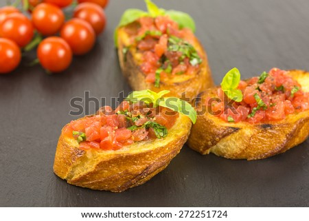traditional italian bruschetta with chopped tomatoes in olive oil and basil garnishing on slate plate - stock photo