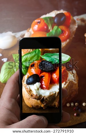 Traditional Italian bruschettas with grilled tomato on wooden background photographing with mobile camera,selective focus - stock photo