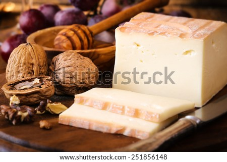 Traditional Italian cheese Taleggio sliced on wooden board and served with grapes, honey and walnuts - stock photo