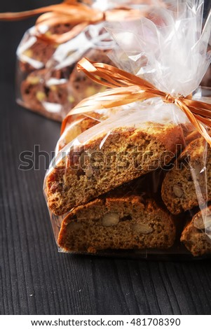 Traditional Italian food. Sweet biscuits cantuccini with almonds. Wrapped in a package with a bow. Dark background