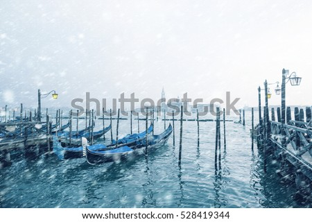 Traditional Italian gondolas moored to the poles in Europe Venice near the city center and Saint Mark square with a background view of the church of San Giorgio Maggiore at cold windy snowy winter day